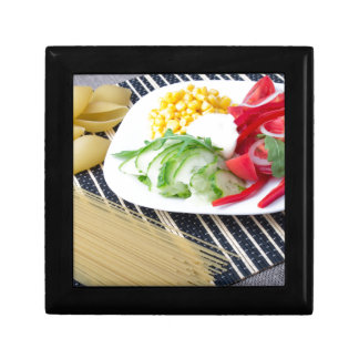 Pieces of fresh raw vegetables on a white plate gift box