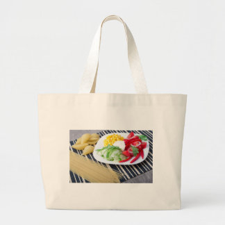 Pieces of fresh raw vegetables on a white plate large tote bag