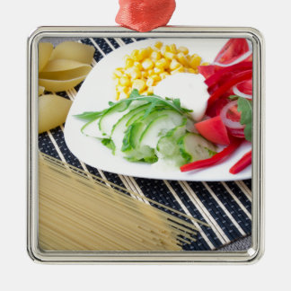 Pieces of fresh raw vegetables on a white plate metal ornament