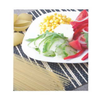 Pieces of fresh raw vegetables on a white plate notepad