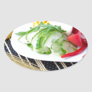 Pieces of fresh raw vegetables on a white plate oval sticker