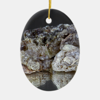 Pieces of natural frankincense resin on a mirror. ceramic ornament