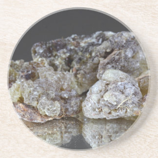 Pieces of natural frankincense resin on a mirror. drink coaster
