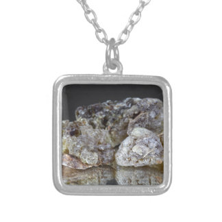 Pieces of natural frankincense resin on a mirror. square pendant necklace