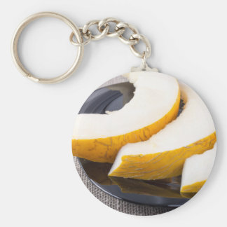 Pieces yellow melon on a black plate keychain