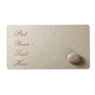 Piedra beige en fondo de la arena etiquetas de envío
