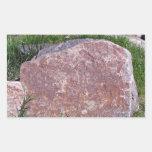 Piedra roja en paisaje verde rocoso etiqueta
