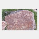 Piedra roja en paisaje verde rocoso etiquetas