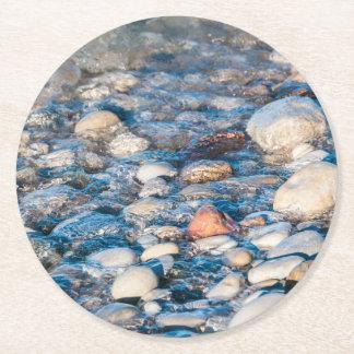 Piedras de la playa en la orilla del lago posavasos desechable redondo