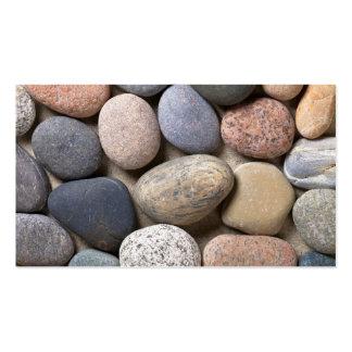 Piedras del guijarro en la arena para el fondo plantilla de tarjeta personal