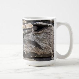 Piedras grandes y pequeñas en una pared taza clásica