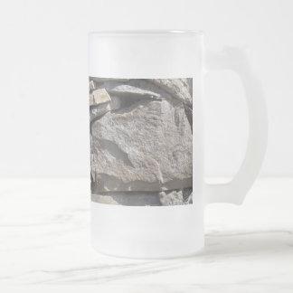 Piedras grandes y pequeñas en una pared taza de cristal