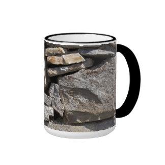 Piedras grandes y pequeñas en una pared taza de dos colores