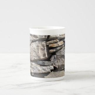 Piedras grandes y pequeñas en una pared taza de porcelana