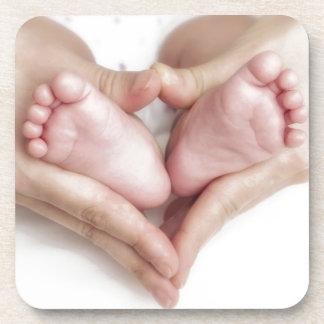 Pies del bebé en manos de la madre posavaso