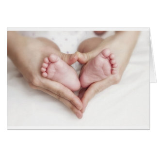 Pies del bebé en manos de la madre tarjeta de felicitación