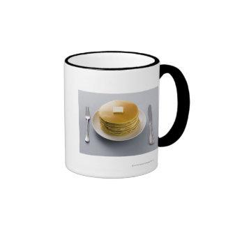 Pila de crepes con mantequilla en una placa taza de dos colores
