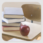 Pila de libros, de manzana, y de escritorio de la pegatina cuadrada