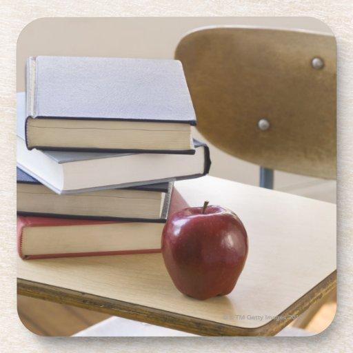 Pila de libros, de manzana, y de escritorio de la posavasos de bebida