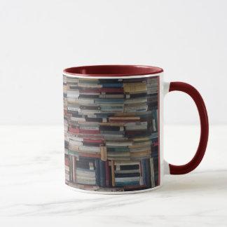 Pilas que se elevan de libros acuñados juntos taza