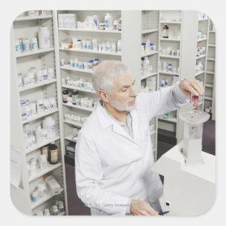 Píldoras de colada del farmacéutico en la cuenta pegatina cuadrada