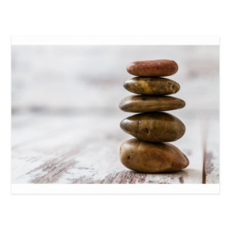 Pile of dark colored stones on white background postcard