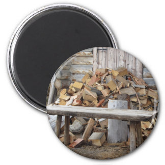Pile of firewood next to hut cabin 2 inch round magnet