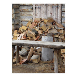 Pile of firewood next to hut cabin postcard