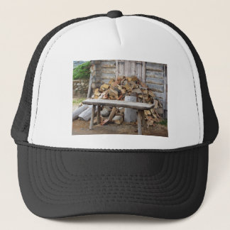 Pile of firewood next to hut cabin trucker hat