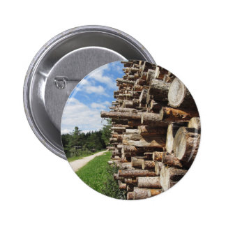 Pile of firewood with forest and sky background pinback button