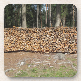 Pile of firewood with forest background drink coaster