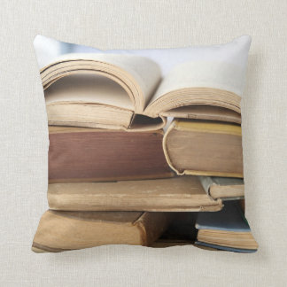 Pile of old books, one open throw pillow