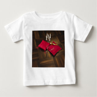 Pillows, candlesticks and champagne on dark parque baby T-Shirt