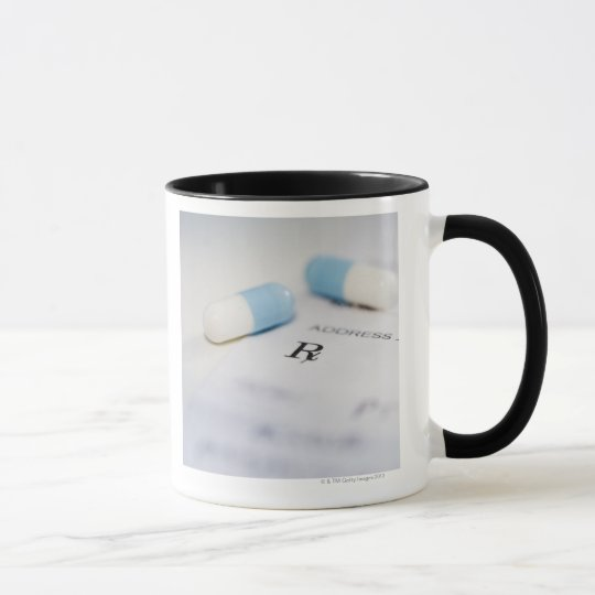 Pills on written prescription mug