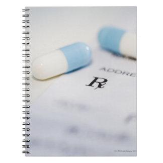 Pills on written prescription spiral notebook