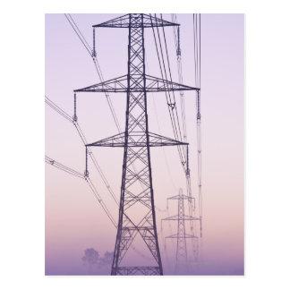 Pilones de la electricidad en niebla en el amanece postal