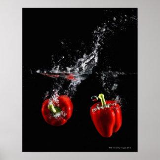 pimienta roja que salpica en agua poster