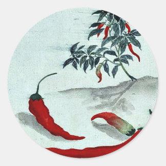 Pimientas rojas con la planta que crece en el fond etiqueta redonda