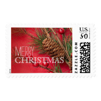 Pine cones and berries decoration on red paper postage