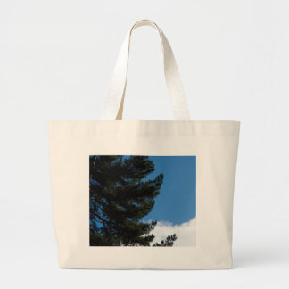 Pine Tree Agains The Blue Sky With Some Cloulds Canvas Bags