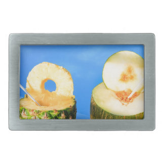 Pineapple and melon fruit with straws at pool belt buckle