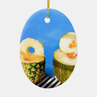 Pineapple and melon fruit with straws at pool ceramic ornament