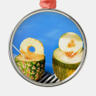 Pineapple and melon fruit with straws at pool metal ornament