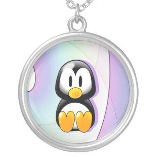 Pingüino adorable del dibujo animado que se sienta collar plateado