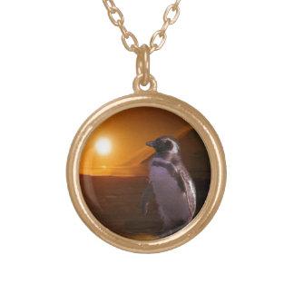 Pingüino de Adelie y puesta del sol antártica Collar Dorado