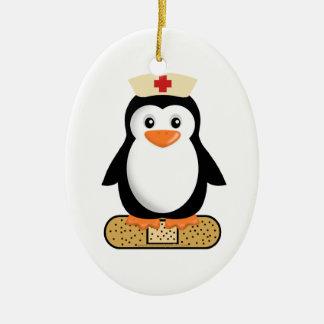 Pingüino de la enfermera (w/bandaid) adorno navideño ovalado de cerámica