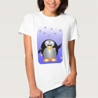 Pingüino del dibujo animado con los copos de nieve playera