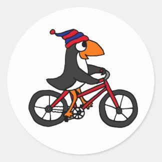 Pingüino divertido que monta la bicicleta roja pegatina redonda
