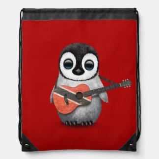 Pingüino que juega rojo de la guitarra de la mochilas