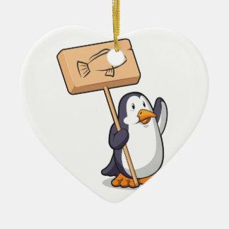 Pingüino que lleva a cabo una muestra de madera adorno navideño de cerámica en forma de corazón